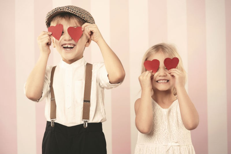 Young boy and girl holding red heart shapes over their eyes